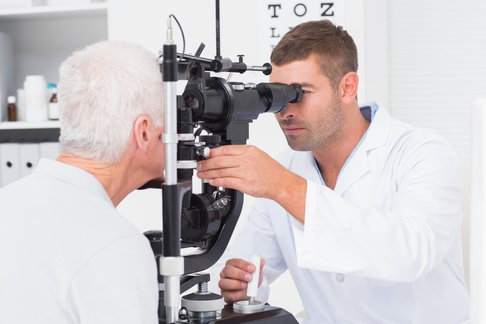 Male optometrist examining senior mans eyes through slit lamp in clinic